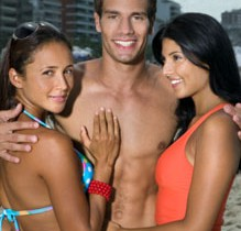 Young man with arms around two young women at beach, portrait